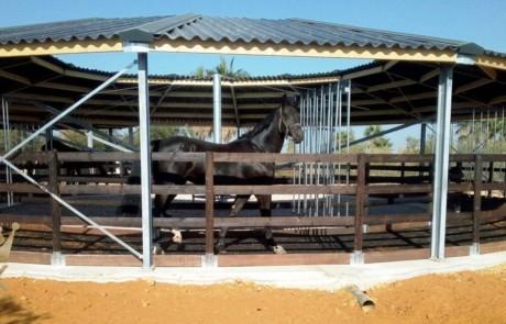 Overdækket skridtmaskine med træ indhegning og vindnet